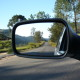 View of a country road through a car's wing mirror.