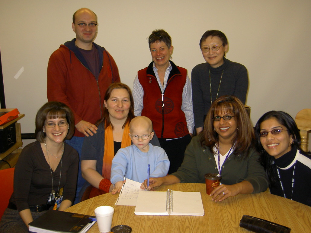 A family is pictured with their medical team, including ophthalmologist, oncologist, nurse specialists and social worker.