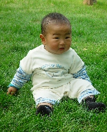 A baby with retinoblastoma relaxes on the grass.