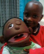 A Kenyan boy plays with a large child puppet that has a removable eye.