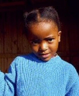 A young African girl smiles shyly.