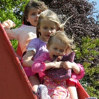 Daisy and her two sisters hug together on their way down a slide.