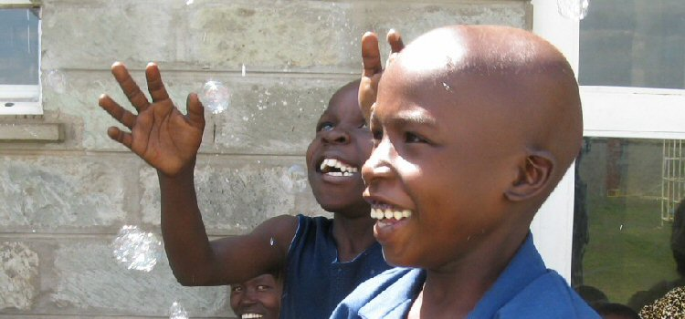Two Kenyan children smile during bubble play at the hospital.