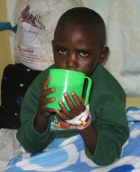 A Kenyan child drinks from a bid green cup.