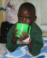 A Kenyan child drinks from a bid green cup.