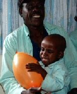 Smiling Kenyan parent and child playing with orange balloon