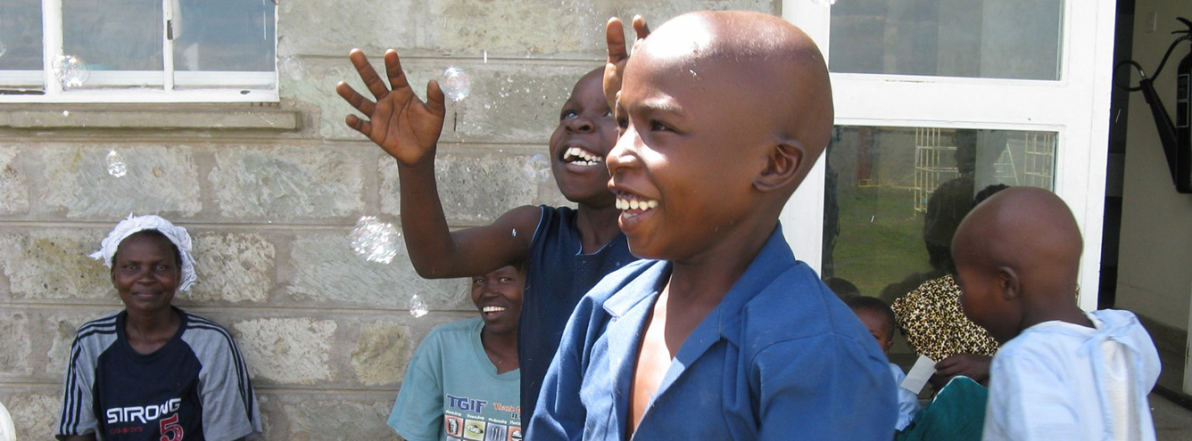 Hospitalized children in Kenya smile while blowing and catching bubbles.