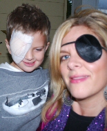 A mother offers upport by wearing an eye patch after her son's surgery.