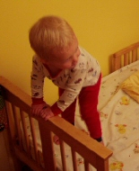 A young child stands on the end of his bed, holding on to the frame.
