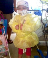 A child in transplant is dressed in protective gown and mask.