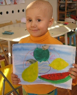 A young girl bald from chemotherapy, displays her painting.