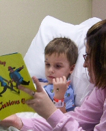 A mother and her hospitalized son read a book together.