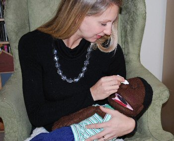 A woman applies pretend drops to a child-sized medical play puppet laying in her lap, cradled in her arm. The child is secured by the woman's left arm, wrapped comfortingly around the shoulders. Her hand rests over the child's arms, which lie on the chest, crossed at the wrists. She applies the drops with her right hand.