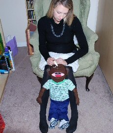 A woman applies pretend drops to a child-sized medical play puppet sitting in a stroller. The child's hands are relaxed down by the side. The head is fully supported by the stroller, and the woman has both hands free to apply the drops, if needed.