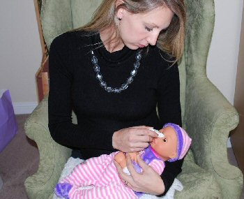 A woman applies pretend drops to a demonstration infant doll laying in her lap and cradled in her arm. Her left arm is wrapped comfortingly around the baby and she holds both arms in place across the chest while applying the drops with her right hand.