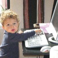 A young Rb survivor sits studiously at the family computer.