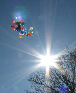 A star-shaped sun flash is set against balloons released into the sky.