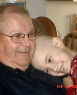 A young girl rests on her grandfather's shoulder.