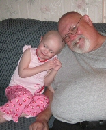 A young girl snuggles up with her grandfather after enucleation surgery.