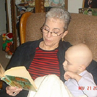 A grandmother reads to her young granddaughter during chemotherapy.