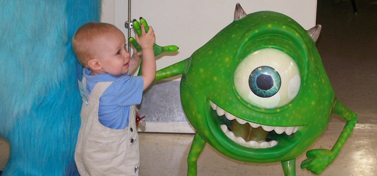 A young child with Rb grasps the hand of Monsters Inc. character, Mike, the one-eye'd figure as tall as the child.