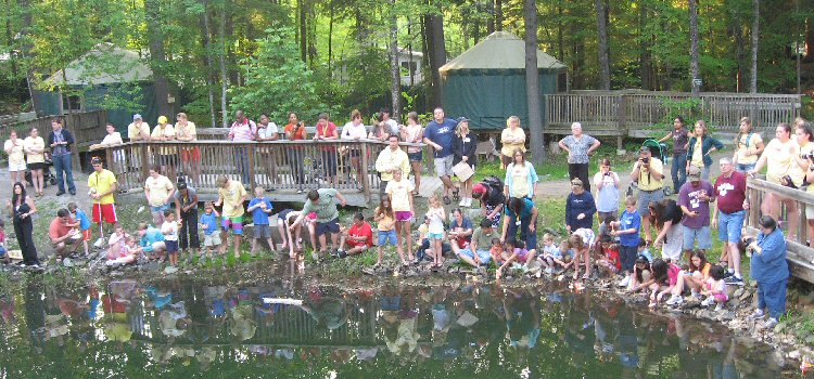 Children launch candle-bearing wish boats on the Wish Pond at Camp Sunshine.