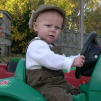 A young child enjoys a green ride-along toy.