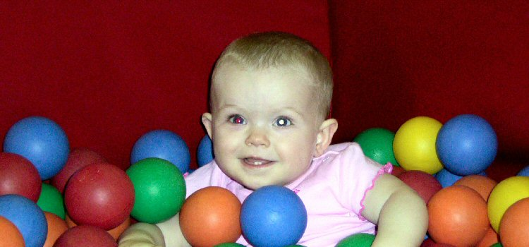 A child with one red pupil and one white pupil smiles while playing in a ball pool.