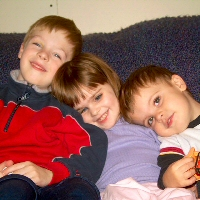 a young girl with retinoblastoma and her brothers relax together.