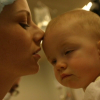A baby receives a loving kiss before a procedure.