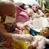 A young girl plays doctor with her doll during her own transplant.