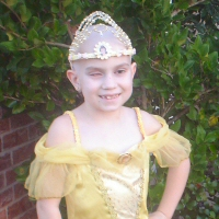 A girl who has lost her hair to chemotherapy and her eyes to cancer smiles radiantly dressed as Belle.