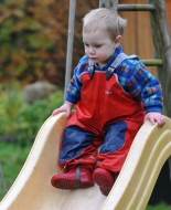 A young boy plays on a slide.
