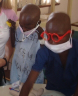 Two young patients in Africa explore medical play equipment.
