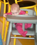 A baby wriggles in her high chair.
