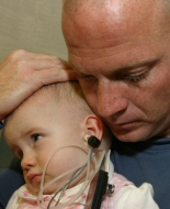 A father comforts his daughter during a procedure.