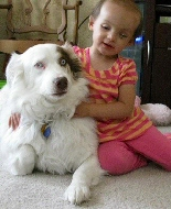 A young girl hugs her dog.