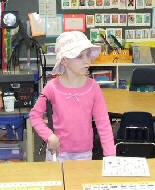 A child wearing a hat explores her classroom.