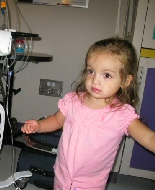 A young girl dances while receiving an infusion.