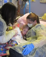 A child is cared for in an isolation room with strict infection control measures.