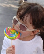 A young girl enjoys a tasty treat while sporting some fashionable shades.