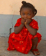 A young African girl crouches with her chin in her hands.