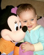 A child with white reflex in both eyes hugs a large Mickey Mouse.