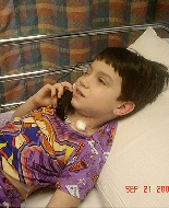 A child talks on the phone from her hospital bed.