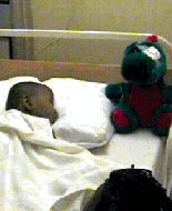 A dinosaur wearing an eye patch watches over a child recovers from surgery.