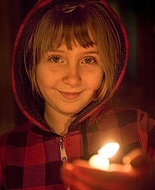 A child shields the flame of a candle in her hands.