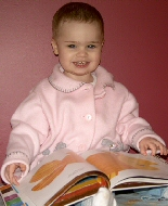 A young girl enjoys a picture book.