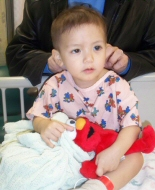 A young boy clutches his elmo plush while awaiting a procedure.
