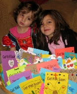 Two girls look at a mountain of encouraging notes and prayers from friends.