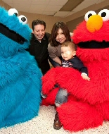 A family enjoys hugs from Elmo and the Cookie Monster.